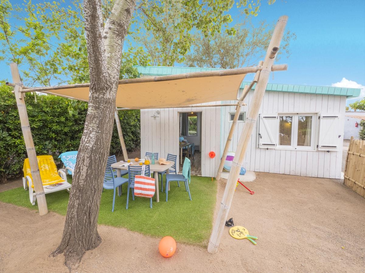 location cabane en bois blanche et bleu avec jardinet dans camping bord de mer à vias plage