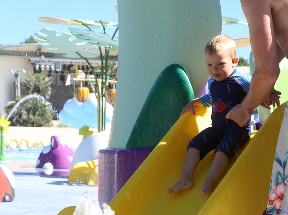 small child slides on a slide in the farret swimming pool