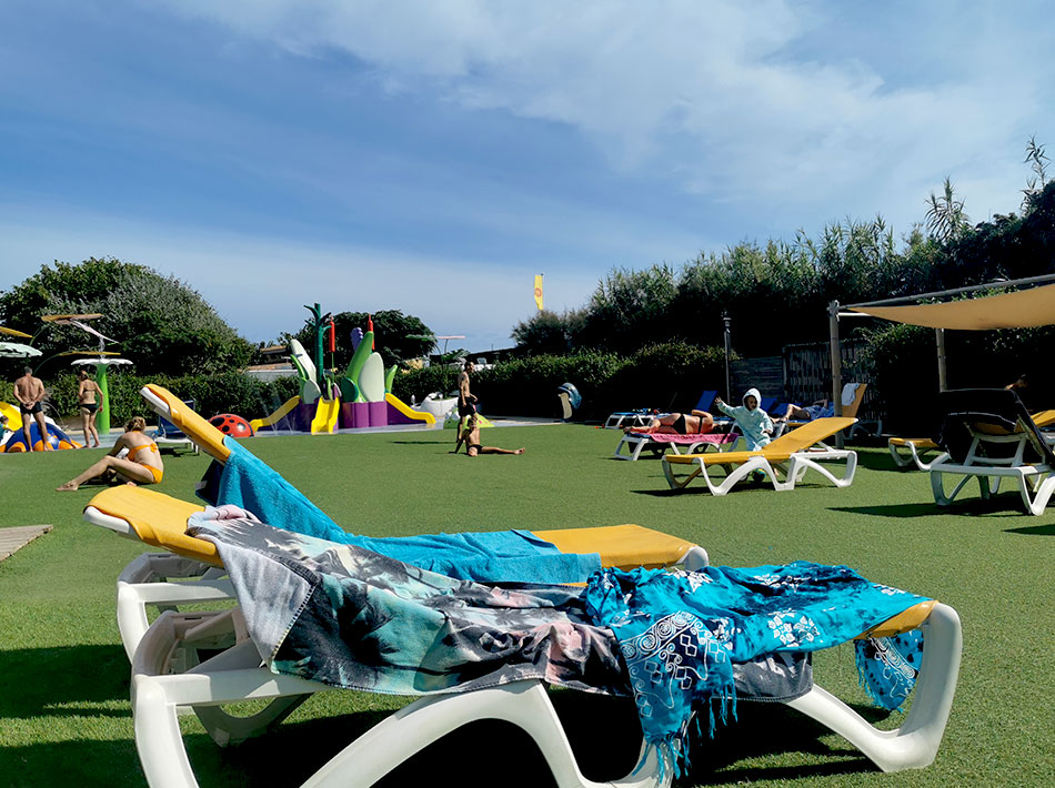 Large sunbathing area with shade cloth in a campsite with swimming pool