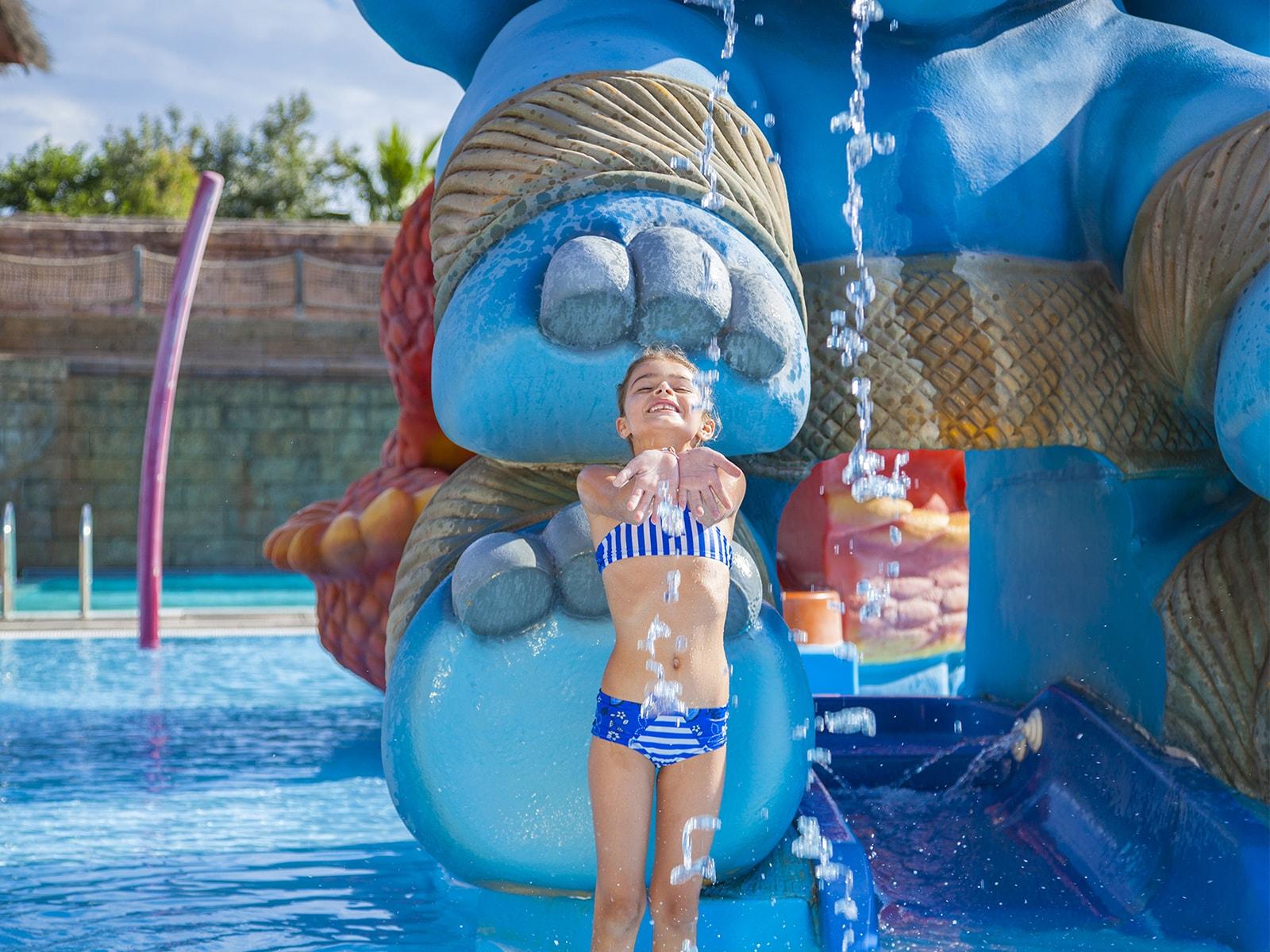 petite fille sous cascade d'eau piscine temple indonésien