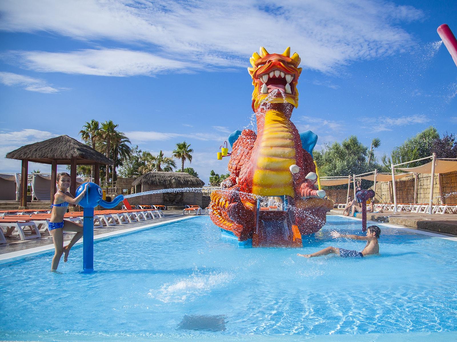 enfants jouant à la bataille d'eau devant jeux d'eau dragon géant