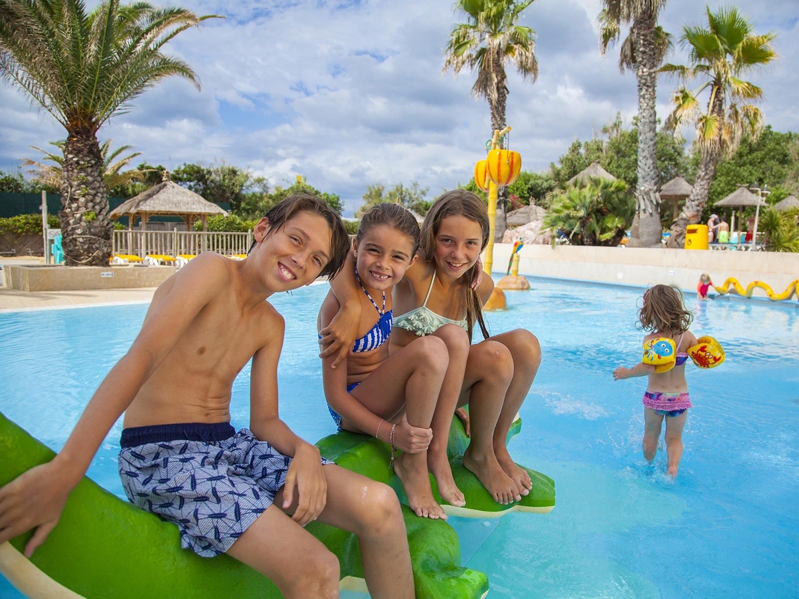 enfants posant sur jeux aquatiques crocodile dans pateaugoire