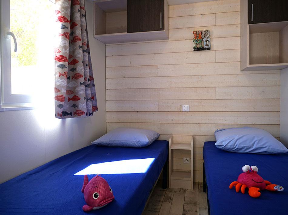 2 chambres pour enfants avec lits simples couverture bleu peluches marines
