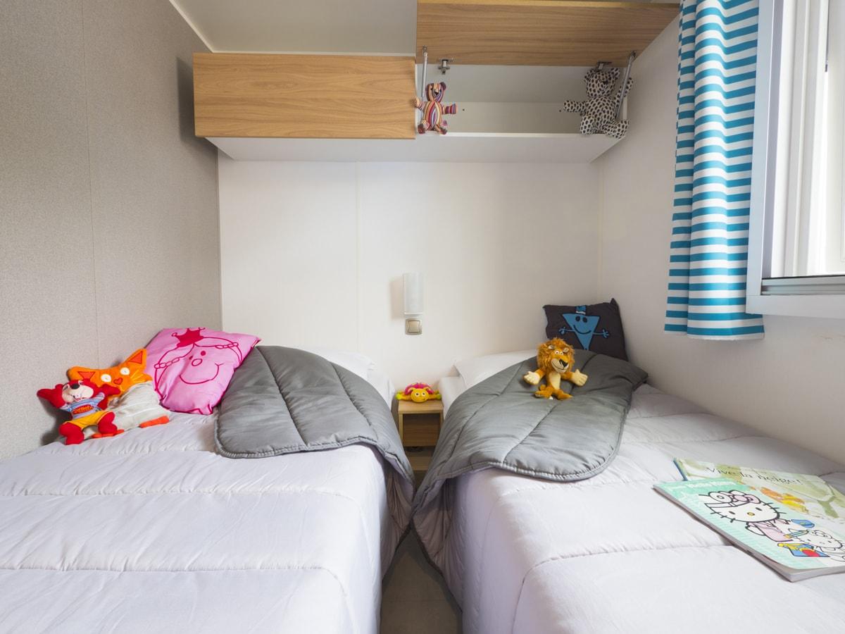 Chambre pour enfants avec deux lits simples et rangement décorée avec goût