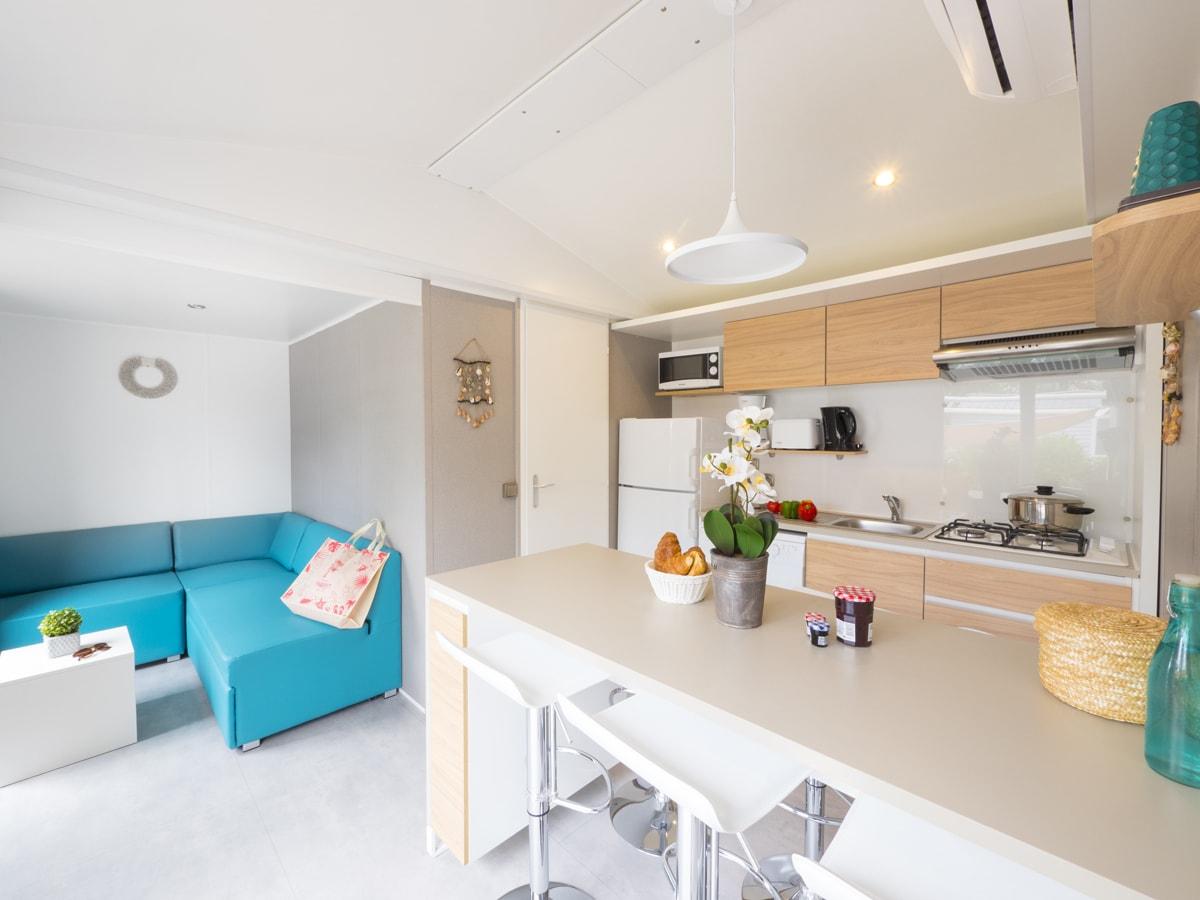 Intérieur mobil-home haut de gamme pour 5 personnes avec îlot centrale et cuisine tout équipée lave vaisselle et télévision