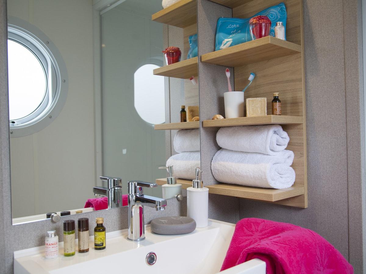 salle de bain spacieuse dans mobil-home de standing au club farret avec rangement et sèche-cheveux