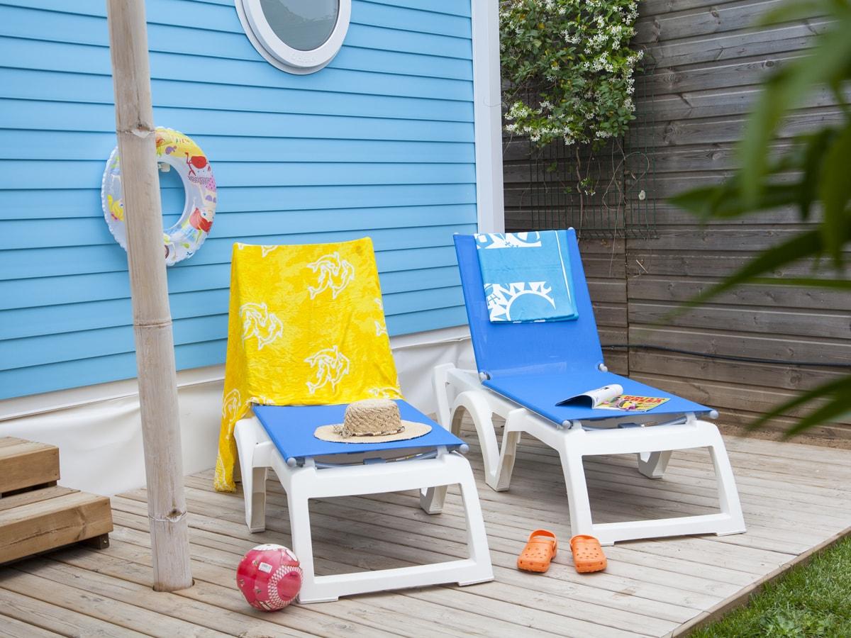Bains de soleil bleus sur terrasse ensoleillée en bois partiellement couverte