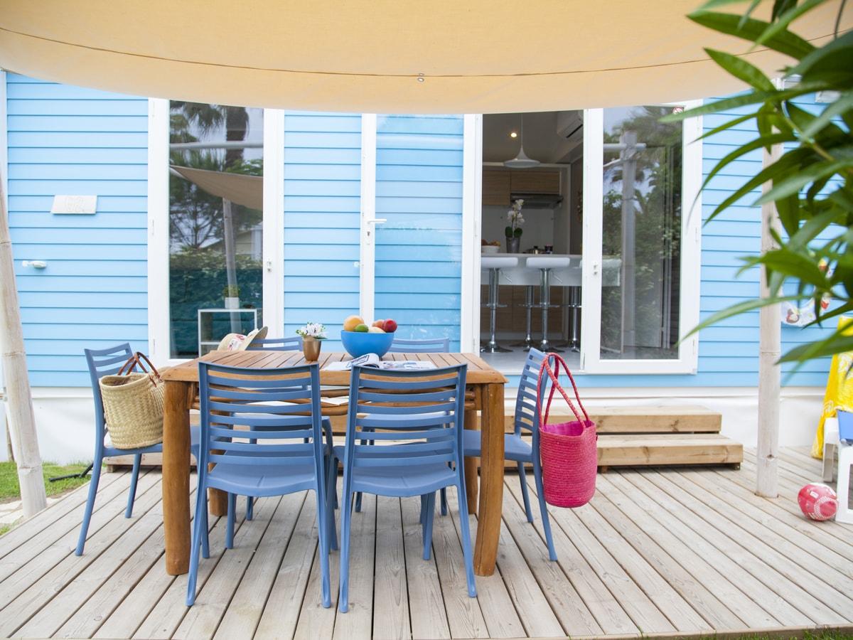 terrasse extérieure en bois avec gazon devant mobil-home bleu quartier côté mer à vias-plage