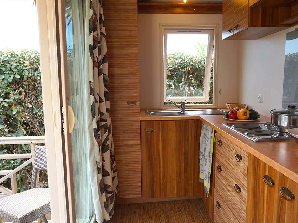 Teak wood kitchen with large window and access to the wooden terrace