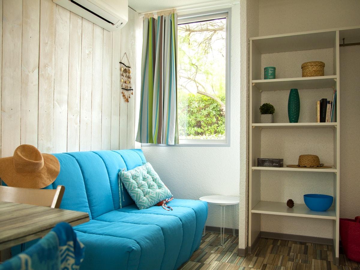 salon cosy décoration soignée avec canapé bleu et salle à manger