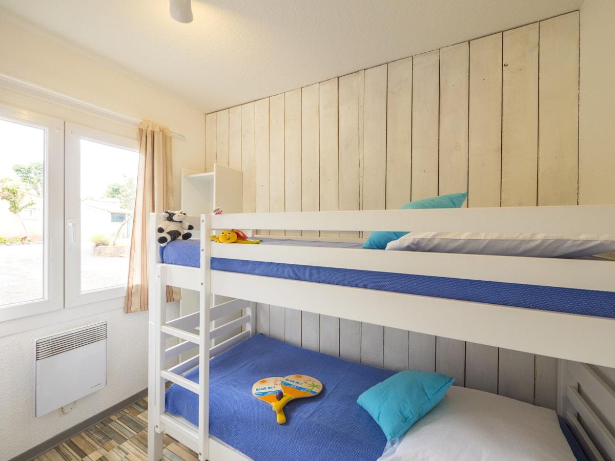 Chambre avec lits superposés pour enfants mur en bois blanc