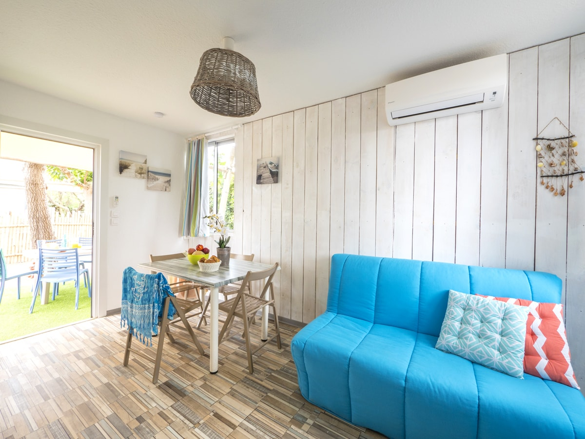 Salon canapé bleu coussins colorés touches de décorations bois