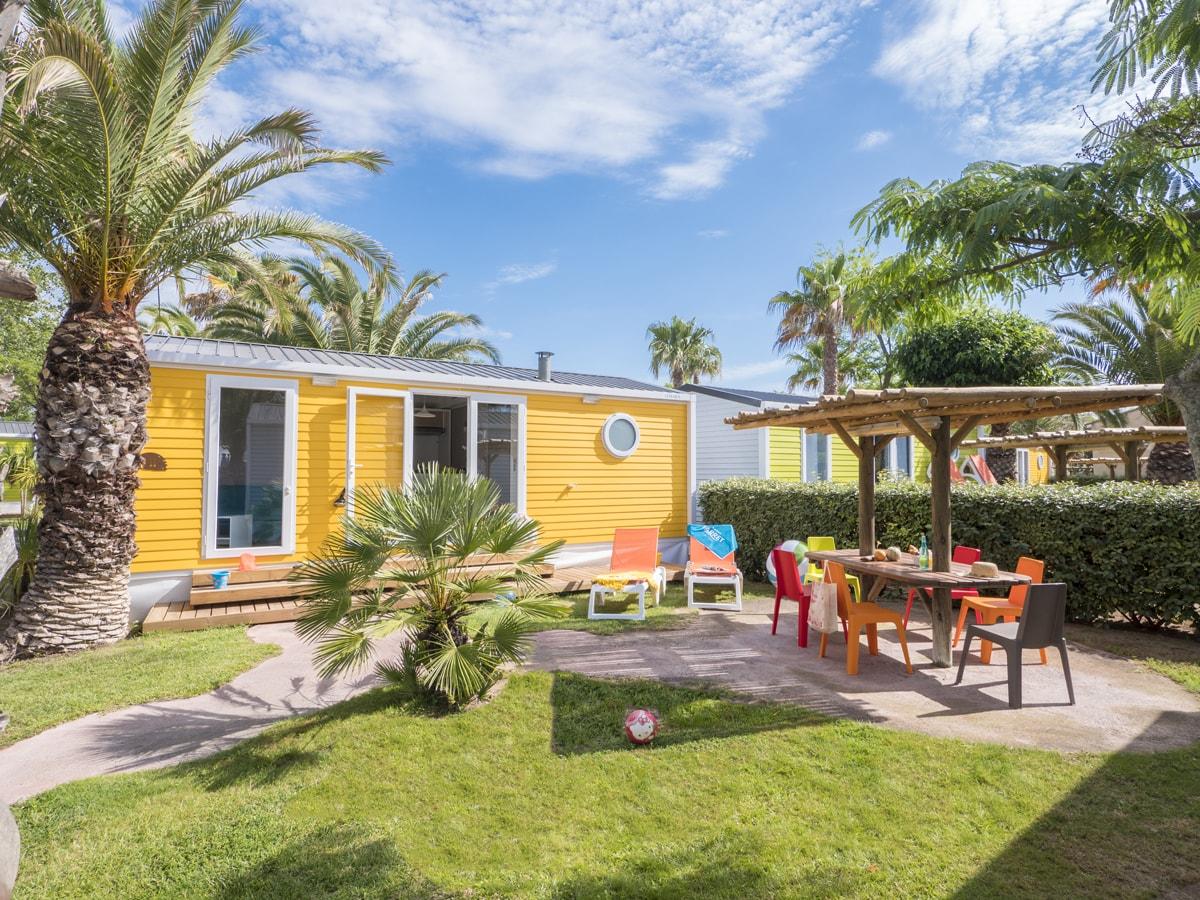 mobil-home jaune avec terrasse extérieur et mobilier camping club farret