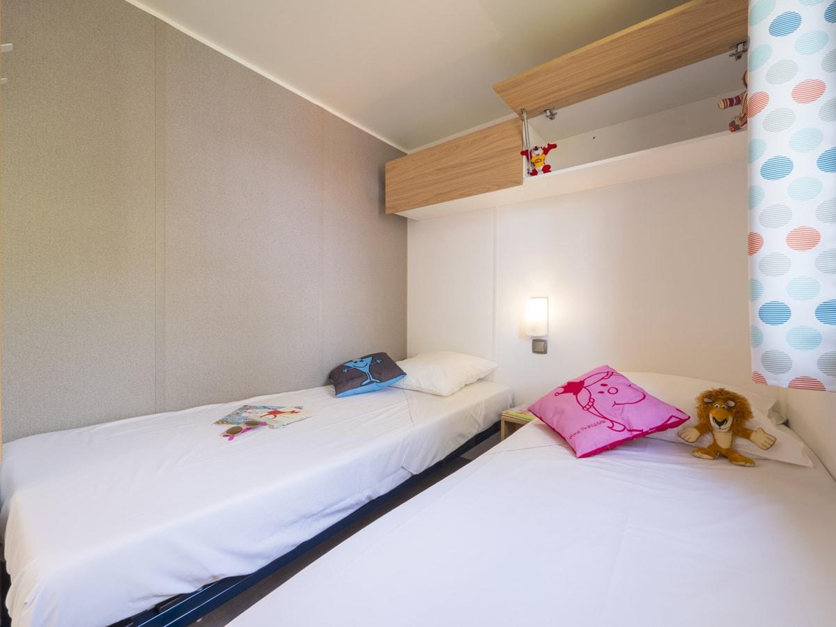 chambre pour enfants tout confort avec deux lits simples et placard de rangement