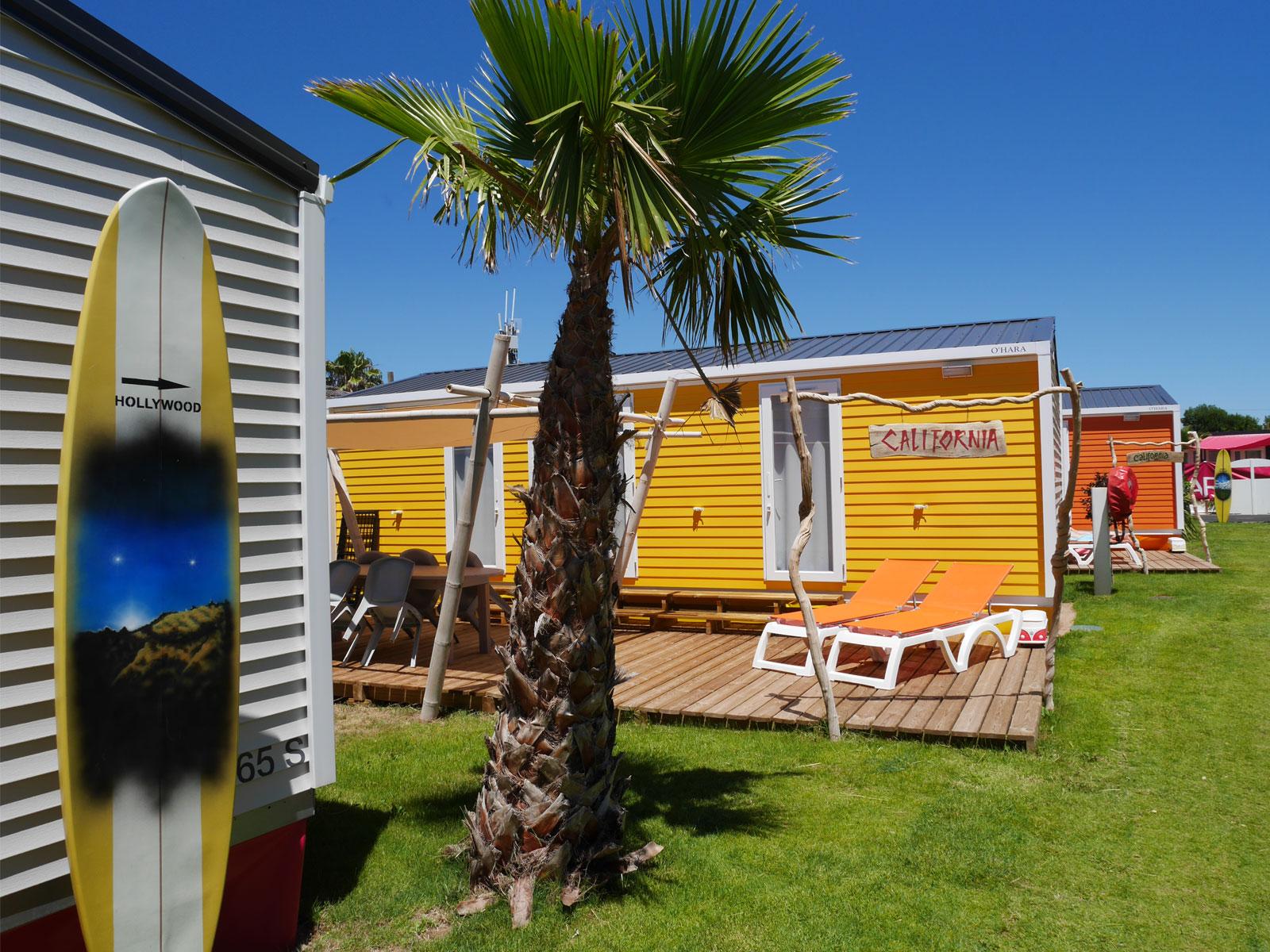mobile home jaune planche de surf et palmier