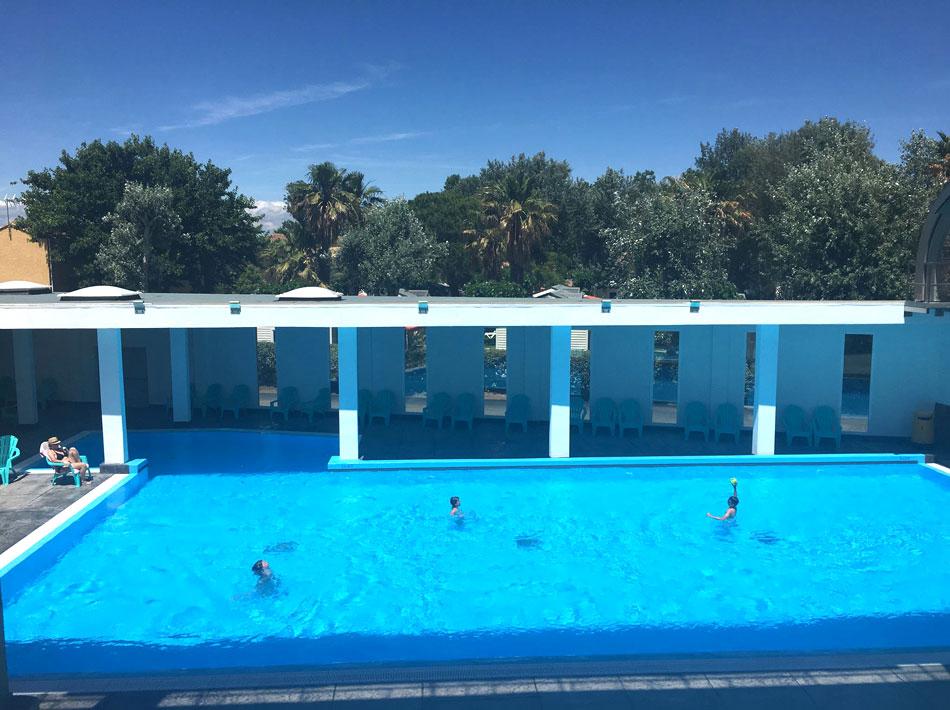 piscine avec grand bassin de nage, vue mer et palmier, dans le sud de la France, vacances en Occitanie