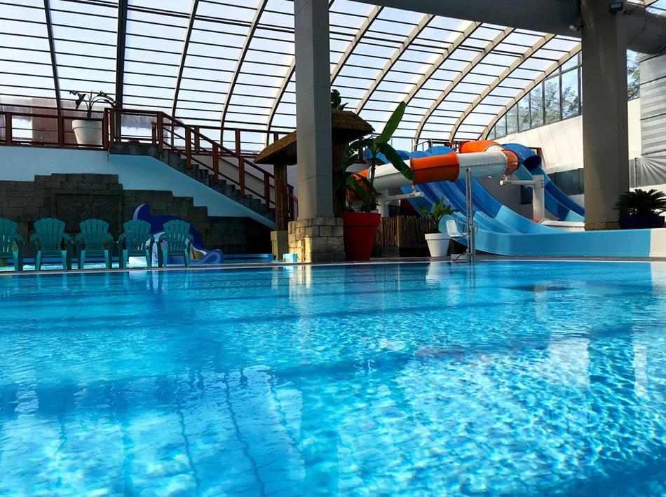 grand bassin de nage avec colonnes et murs blancs inspiration Grèce